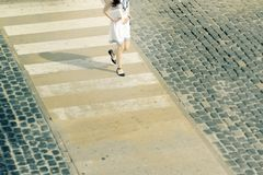 Young woman in a summer dress from above walking at a crosswalk. Empty copy space royalty free stock image