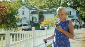 Young woman in summer dress enjoys smartphone on city street. A woman is using a smartphone. It stands on the street near a white fence, behind the American flag stock video footage