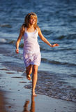 Young woman in summer dress jumping on sand. Stock Image