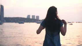 Young woman in summer dress standing on the beach of tropical city and looking to a sea at sunset.  stock footage