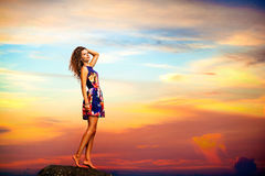 Young woman in summer dress standing on a rock. Carefree woman dancing in the sunset on the rock. Vacation vitality healthy living concept Royalty Free Stock Photography