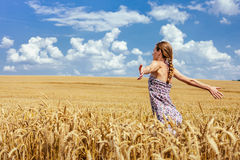 Young woman in summer dress standing in wheat field. Young woman in summer dress standing in the field with raised arms Royalty Free Stock Photos