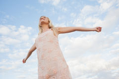 Young woman in summer dress stretching arms against sky Stock Photography