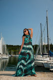 Young woman with summer dress and sunglasses walks pier of marin Stock Photos