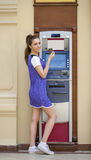Young woman in summer dress using an automated teller machine Royalty Free Stock Photo