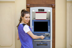 Young woman in summer dress using an automated teller machine Stock Photo