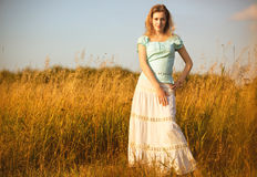 Young woman on a summer field. Red sunset light Stock Image