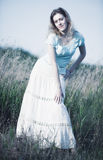 Young woman on a summer field. Soft blue tint Stock Image