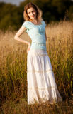 Young woman on a summer field. Red sunset light Stock Photography