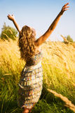 Young woman in a summer field. Young woman stretching up in a summer field Stock Images
