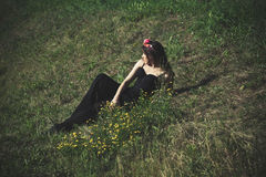 Young woman at summer field. Young woman in black dress and wreath of flowers lie on summer grass full body shot Stock Photo