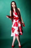 Young woman in summer flowery dress on green Stock Photography