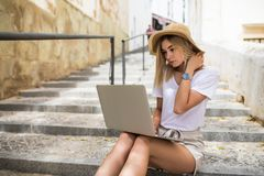 Young woman in summer hat with laptop sitting on stairs on summer street stock image