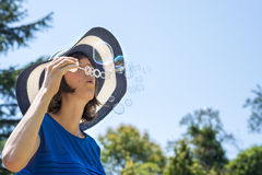 Young woman on summer holidays blowing soap bubbles Royalty Free Stock Photo