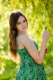 A young woman in a summer park. A beautiful young  girl in the green outdoor nature background Stock Photography