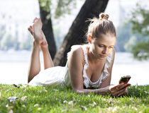 Young woman on the summer park. Portrait of young woman lying on a green lawn Royalty Free Stock Images