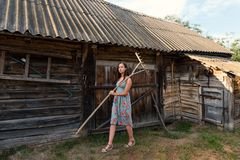 A young woman in a summer retro sarafan dress goes around the yard along the sheds and old rural buildings with rakes on the shoul royalty free stock images