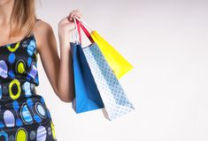 Young woman in summer shopping with shopping bags on gray background. Happy royalty free stock photos