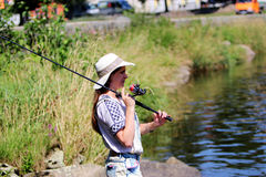 Young woman with summer sprouts and dungarees while fishing Stock Photo