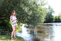 Young Woman fishing on a river in Germany Stock Photography