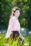 Young woman on a summer sunny day walking in field of flowers. Young woman on a summer sunny day walking in the field of flowers with high grass Royalty Free Stock Images
