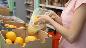 Young woman picking an oranges from box at supermarket royalty free stock images