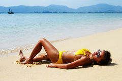 Young woman sun bathing on a sandy beach of Thailand Stock Photos