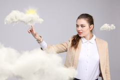 Young woman and sun shining out from behind the clouds, cloud computing or weather concept Stock Image