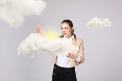 Young woman and sun shining out from behind the clouds, cloud computing or weather concept Royalty Free Stock Images
