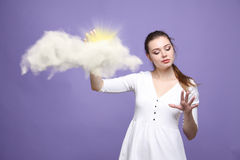 Young woman and sun shining out from behind the clouds, cloud computing or weather concept Royalty Free Stock Image