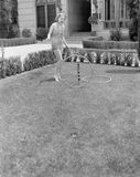 Young woman in a sun suit playing with rings in the yard Stock Photography