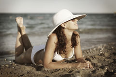 Young woman sunbathes laying on sand. Stock Image