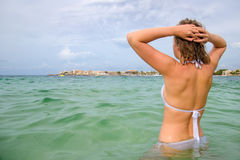Young woman sunbathes in the sea. Stock Photos