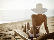 Young woman sunbathes sitting on sunbed. Stock Photo
