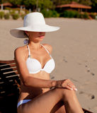 Young woman sunbathes sitting on sunbed. Young woman in white swimsuit sunbathes sitting on sunbed Royalty Free Stock Image