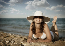 Young woman sunbathes sitting on sunbed. Royalty Free Stock Images