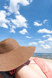 Young woman sunbathing on a beach with a brown hat. Sea and a bl Royalty Free Stock Photography