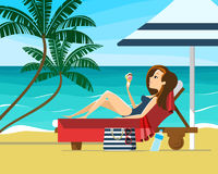 Young woman sunbathing on a beach. Girl relaxing on a lounger under parasol on a tropical beach Stock Photo