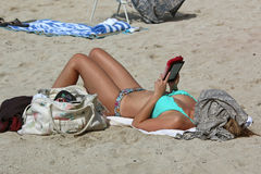 Young woman sunbathing. On beach with head covered and reading her electronic book Royalty Free Stock Image