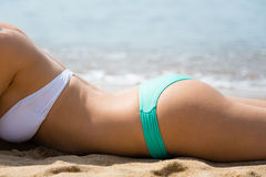 Young woman sunbathing on the beach Royalty Free Stock Image
