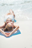 Young woman sunbathing on beach Royalty Free Stock Photography