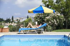 Young Woman Sunbathing In Bikini. On Sunbed By Swimming Pool stock image