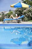 Young Woman Sunbathing In Bikini. On Sunbed By Swimming Pool royalty free stock photos