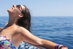 Young woman sunbathing on boat. Close-up of smiling woman in sunglasses sunbathing while leaning on shipboard. Copy space area Royalty Free Stock Photo