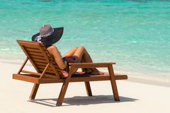 Young woman sunbathing on lounger at tropical beach Royalty Free Stock Photos