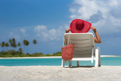 Young woman sunbathing on lounger at tropical beach Royalty Free Stock Images