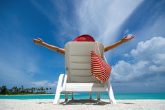 Young woman sunbathing on lounger at tropical beach Stock Images