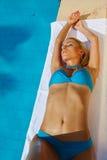 Young woman sunbathing. A young woman sunbathing near swimming pool Stock Photos