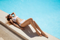 Young woman sunbathing near swimming pool. Young woman in white bikini sunbathing near swimming pool Royalty Free Stock Photos