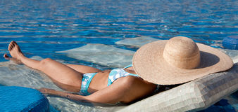 Young Woman Sunbathing in the Pool. Young Woman in Bikini Sunbathing by the Pool in a summer vacation Stock Images